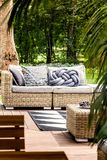 Comfortable couch on patio. Comfortable rattan couch on a sunny patio of a calm summer house during the weekend royalty free stock images