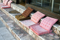 Comfortable Cushion Seats Outside Cafe. Faded but comfortably padded cushion seats on stone steps outside a Greek cafe, Greece stock photography