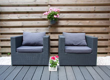 Comfortable design furniture. In a modern garden with summer flowers Stock Photos