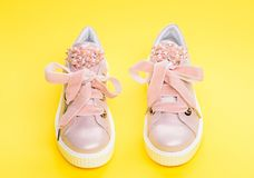 Comfortable footwear concept. Cute shoes on yellow background. Pair of pale pink female sneakers with velvet ribbons. Footwear for girls or women decorated royalty free stock image