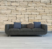 Comfortable grey sofa with a textured stone wall Royalty Free Stock Photos