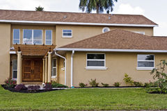 Comfortable Home. Tan house with covered walkway to front door Stock Photo