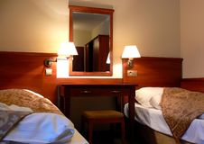 Comfortable hotel bedroom. A view of two beds in a hotel bedroom separated by a large nightstand, mirror and wall lamps Stock Images