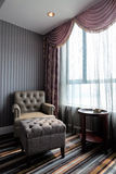 Comfortable hotel room corner. Leather chair and tea table by the window Stock Photos