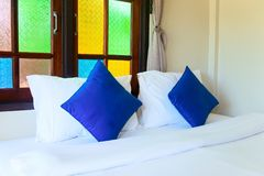 Comfortable king bed in hotel room interio. R with blue pillows and bright color window glass Royalty Free Stock Photo