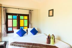 Comfortable king bed in hotel room interio. R with blue pillows, bright color window glass and towels on a bed Stock Image