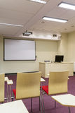 Comfortable learning environment. Part of a lecture room with a view on a board an lecturer desk Royalty Free Stock Photo