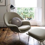 Comfortable light green armchair by window in light filled room stock images