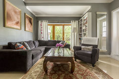 Comfortable living room with classic coffee table. Comfortable living room interior with gray corner sofa and classic coffee table Royalty Free Stock Image