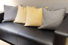 Comfortable and Modern Leather Sofa in Living Room. Beautiful Modern Leather Cozy Sofa with Gray and Yellow Cushion Standing in A Living Room Stock Images