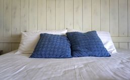 Comfortable throw cushion on white pillows on the bed. Comfortable navy color throw cushion on white pillows on the bed with white stained timber plank stock image
