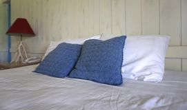 Comfortable throw cushion on white pillows on the bed. Comfortable navy color throw cushion on white pillows on the bed with white stained timber plank stock photography