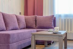 Comfortable new sofa. Cozy comfortable new sofa near table in modern room Stock Photography