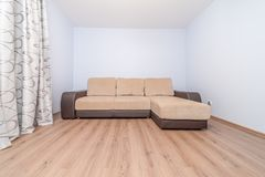 Comfortable new sofa. Cozy comfortable new sofa standing in empty modern room Stock Photography