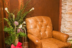 Comfortable old leather chair. A view of a comfortable, stuffed leather chair next to a decorative green plant in a wood-paneled room Royalty Free Stock Images