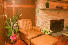 Comfortable old leather chair. A view of a comfortable, stuffed leather chair next to a decorative green plant and a living room fireplace Stock Photography