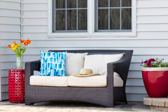 Comfortable outdoor living area on a brick patio. With a deep seating settee and cushions flanked by red ceramic pedestal table and flowerpot with spring Stock Photography
