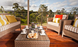 Comfortable outdoor wicker furniture. With striped cushions on a wooden deck overlooking a garden with a low table set for tea and cookies Stock Image