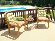 Comfortable Patio. Two comfortable chairs on a patio overlooking a pool in the backyard Stock Photos