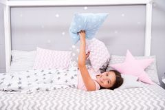 Comfortable pillow. Girl smiling child lay bed star pattern pillows and plaid bedroom. Bedclothes for children. Girl kid. Waking up morning. Modern fashionable stock photo