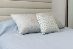 Comfortable pillows on the light blue bed Stock Photos