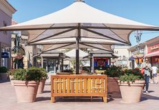Newport Beach, CA, USA - February 19, 2018: Outdoor bench, potted plants, and large shade umbrella. A comfortable place to rest at Fashion Island shopping mall Stock Photography