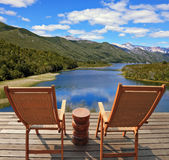 A comfortable place. Two wooden chairs - on a wooden platform. Charming rural idyll. Clouds reflected in the smooth water of the river. A comfortable place to Stock Photos