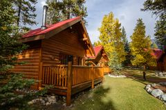 Comfortable quiet wooden hotel at the multicolored fall forest Stock Photo