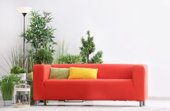 Comfortable red sofa. With pillows in room Royalty Free Stock Photos