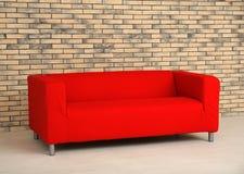 Comfortable red sofa near wall. Comfortable red sofa near brick wall Stock Image