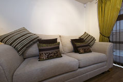Comfortable settee. Large modern comfortable sofa with cushions and decoration Stock Images