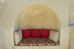 Comfortable sofa with pillows outdoors inside the wall in luxury arabian style hotel Royalty Free Stock Photography