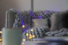 Comfortable sofa with plaid and Christmas lights in room. Comfortable sofa with plaid and Christmas lights in living room stock photo