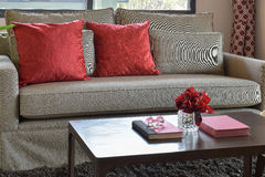 Comfortable sofa with red pillows and red book on wooden table Stock Photos