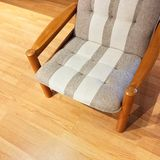 Comfortable striped armchair on a wooden floor Royalty Free Stock Images