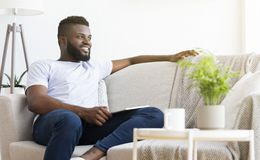 Free Comfortable Weekend. Peaceful African Man Resting At Home Stock Photography - 153803272