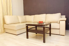 Comfortable white leather corner sofa with coffee table. Stock Images