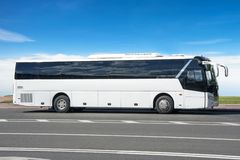 Comfortable white tourist bus on the highway in travel royalty free stock image