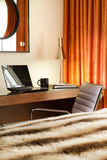 Comfortable workplace in the hotel room. With laptop, notebook, lamp and a cup of coffee on the table Stock Photo