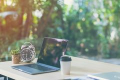 Comfortable workplace, Office desk with blank screen laptop and clock, plant, Nature light bokeh background. Startup at work in the morning, coffee shop, Co royalty free stock image