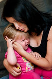 Comforting a Crying Infant. Mother comforting her crying infant baby girl stock photo