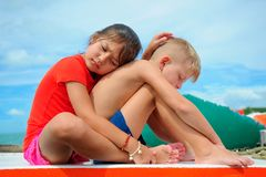 Comforting a friend. Young girl hugs her adorable boy.  Royalty Free Stock Image