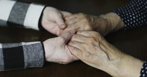 Close-up of adult hands stroking senior female hands with deep wrinkles. Comforting hand. Close-up of adult hands stroking senior female hands with deep stock footage