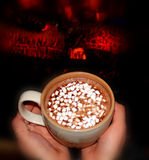 Comforting hot chocolate by the fireplace. Royalty Free Stock Images