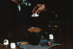 Comforting Mug of Hot Chocolate on Rustic Table with Female Hand Picking Marshmallows in Background stock photography