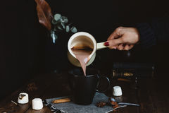 Comforting Scene of Female Pouring Hot Chocolate Drink from Milk Pan into Black Mug on Rustic Table Royalty Free Stock Photos