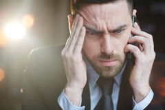 Comfused-Geschäftsmann Calling durch Smartphone Stockfoto