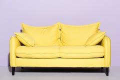 comfy κίτρινος καναπές μπροστά από στοκ εικόνες