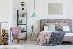 Comfy armchair in the corner. Pink comfy armchair placed in the corner of teen girl`s room Stock Image