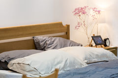 Comfy bed with wooden heardboard. With white side bed lamp in a white bedroom Royalty Free Stock Photo